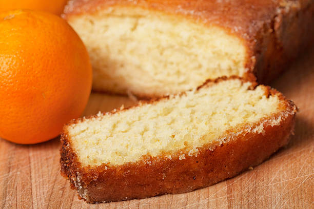 Foto de um bolo de laranja cortado com uma laranja do lado