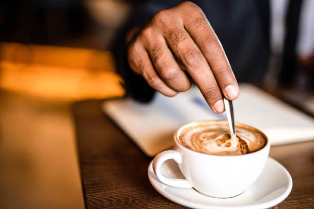 Foto de uma mão masculina mexendo um cappuccino em uma xícara branca