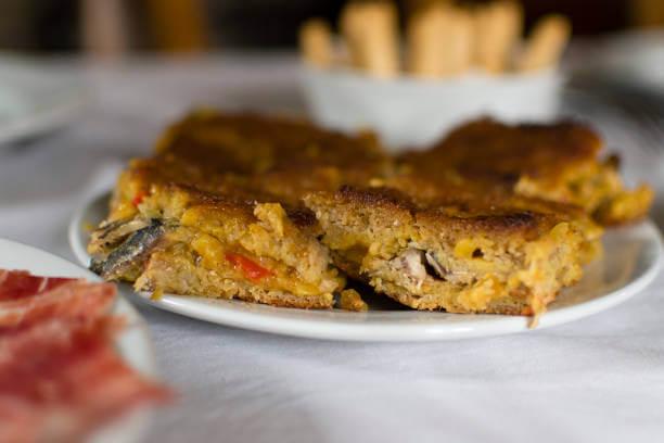 Foto de um pedaço de torta de sardinha em um prato branco