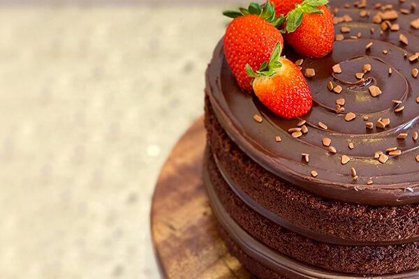 Foto de um naked cake de chocolate sobre uma tábua de madeira