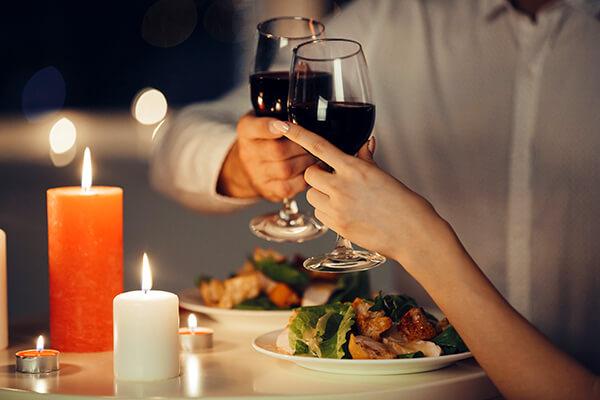 Foto de casal brindando em jantar romântico a luz de velas