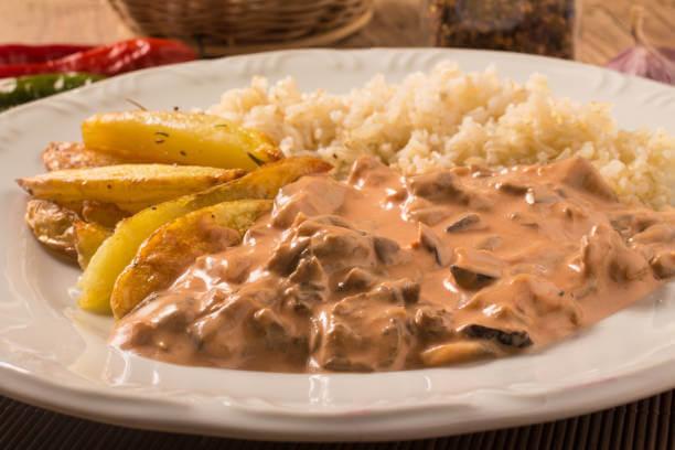 Foto de prato de estrogonofe vegano de shiitake acompanhado de arroz e batatas