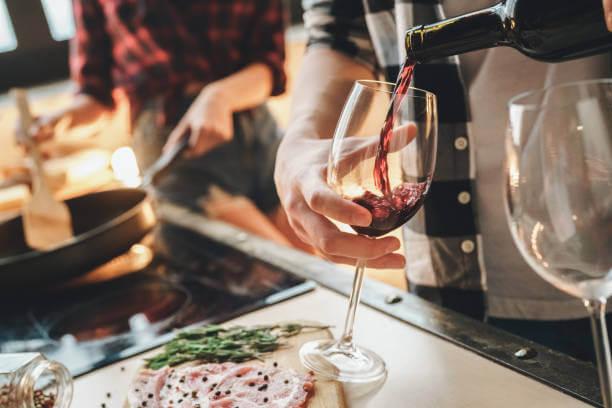 Foto de uma pessoa enchendo uma taça com vinho e outra cozinhando ao fundo