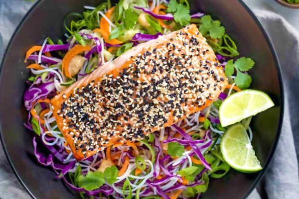 Foto de salmão com crosta de gergelim sobre salada e um prato preto
