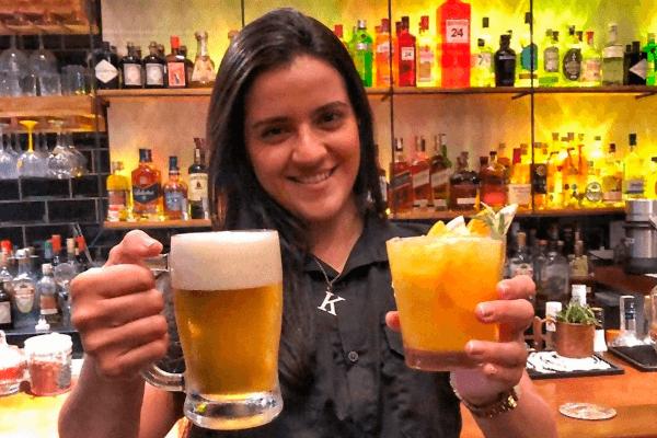 Mulher segurando uma caneca de chope e um copo de drink