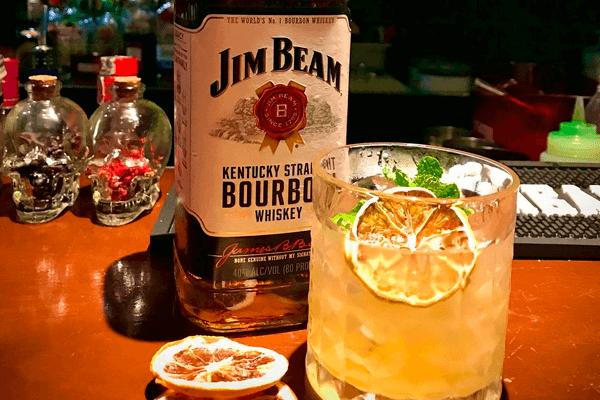 Drink Solozzo feito com Bourbon, syrup de gengibre, suco de limão e limão desidratado