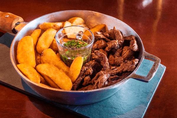Filé Uruguai - cortes de filé bem temperado, acompanhados de batatas rústicas e molho chimichurri